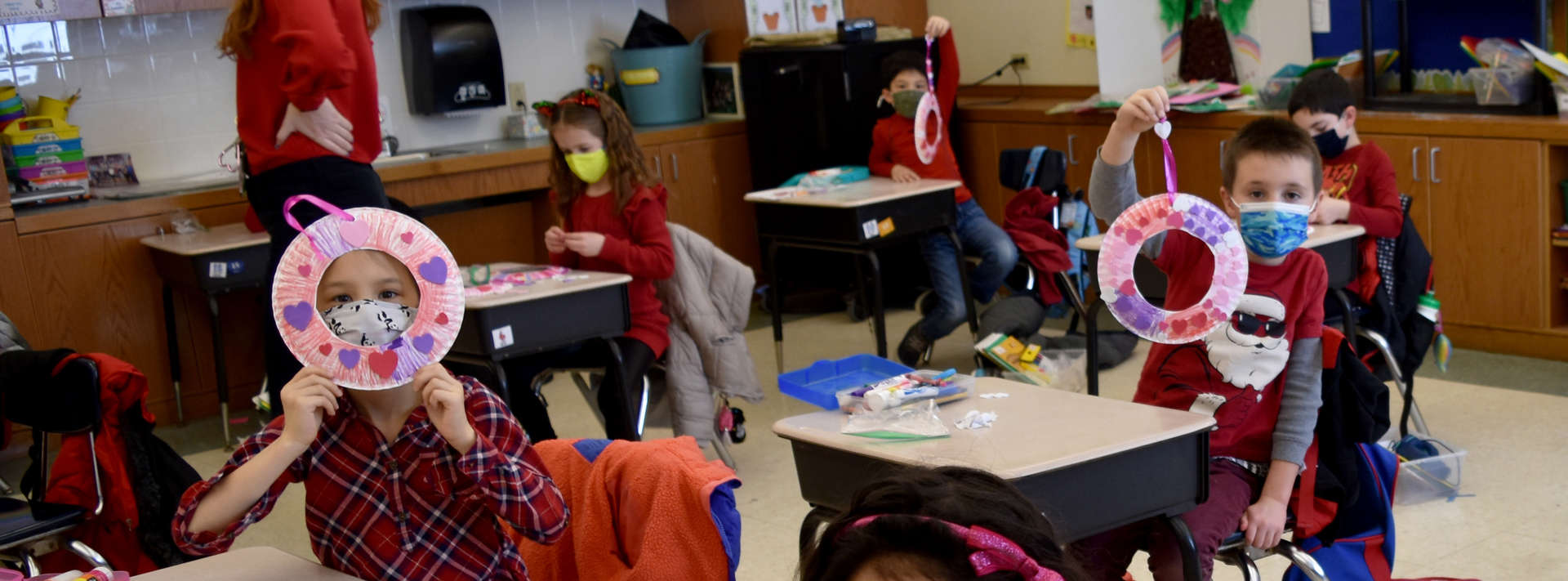 1st grade students show off their Valentine crafts