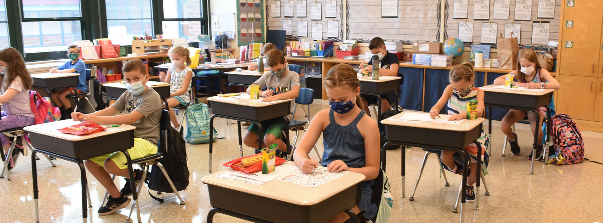 3rd grade students sit at desks in class