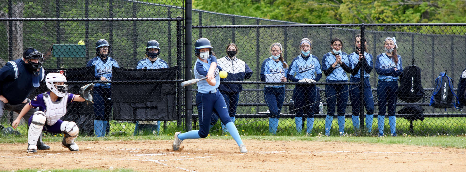 Girl hitting a softball while teammates look on