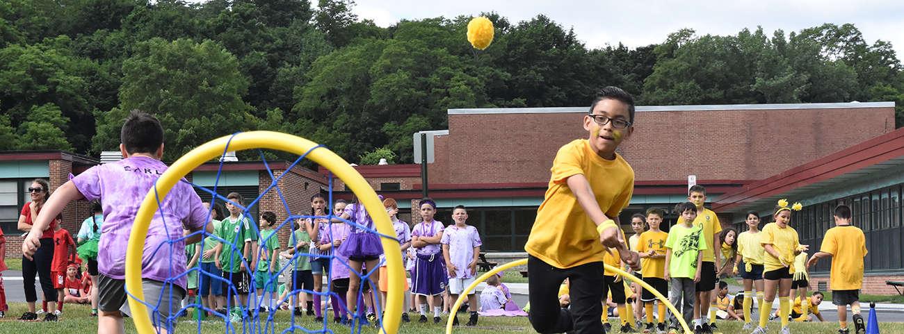 Boy throws ball in hoop.