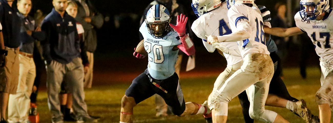 Running back carrying ball in football game