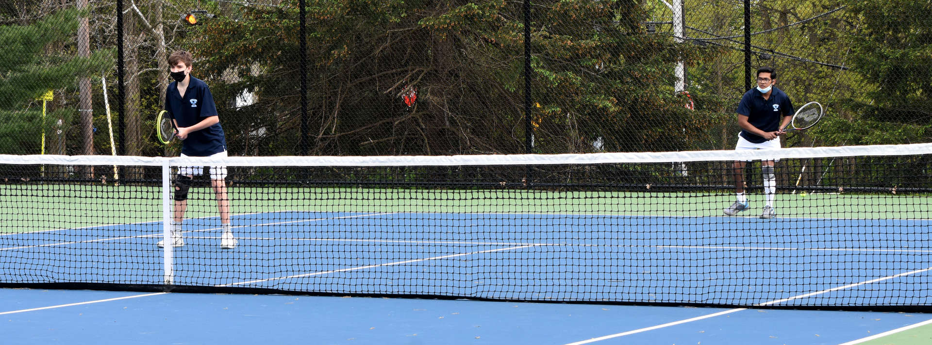 2 male students playing tennis