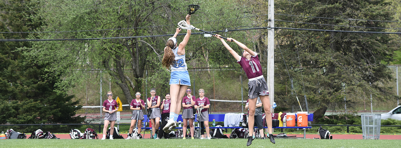 Girl lacrosse player catching ball.