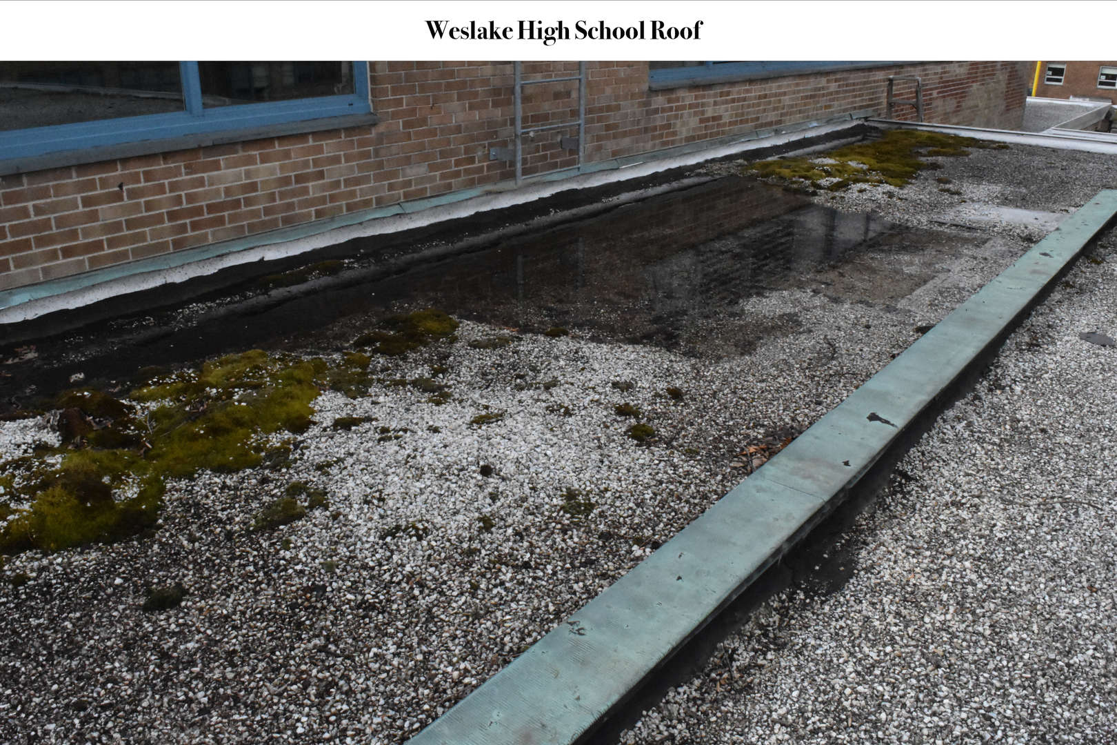 WHS Roof before renovation covered in gravel and flood water