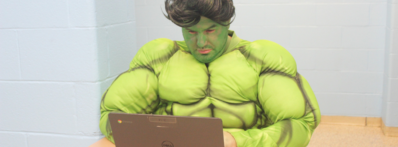 Teacher dressed in Hulk costume using a computer