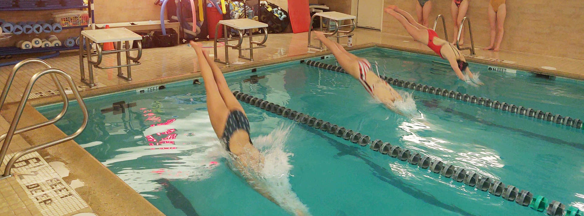 3 swimmers diving into pool