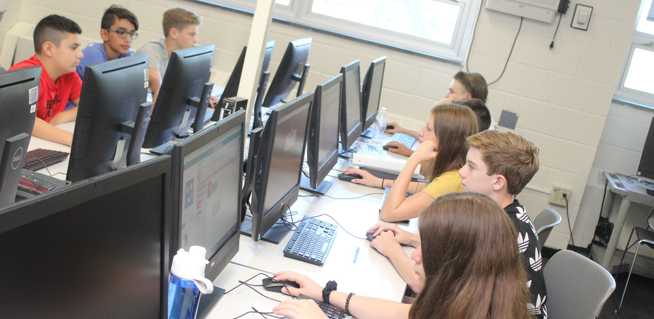 Four Students lined up in front of computers