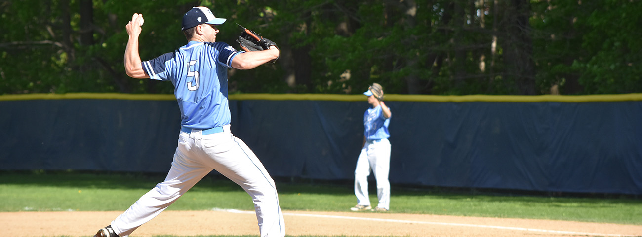 Pitcher throwing ball at baseball game.