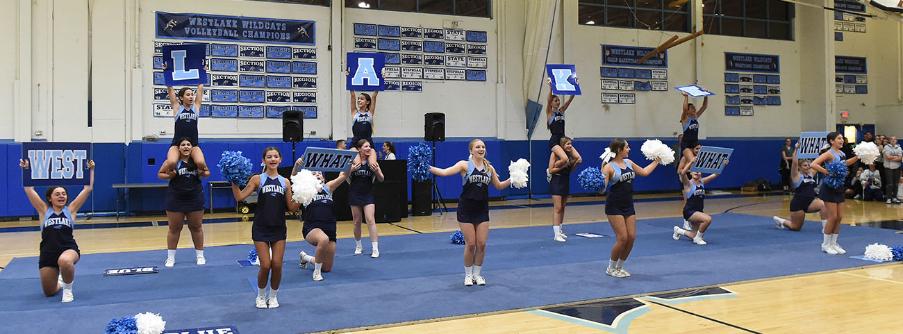 cheerleading team performing stunts in gymnasium