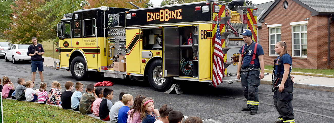 Volunteer Firefighters stand in front of truck and answer student questions