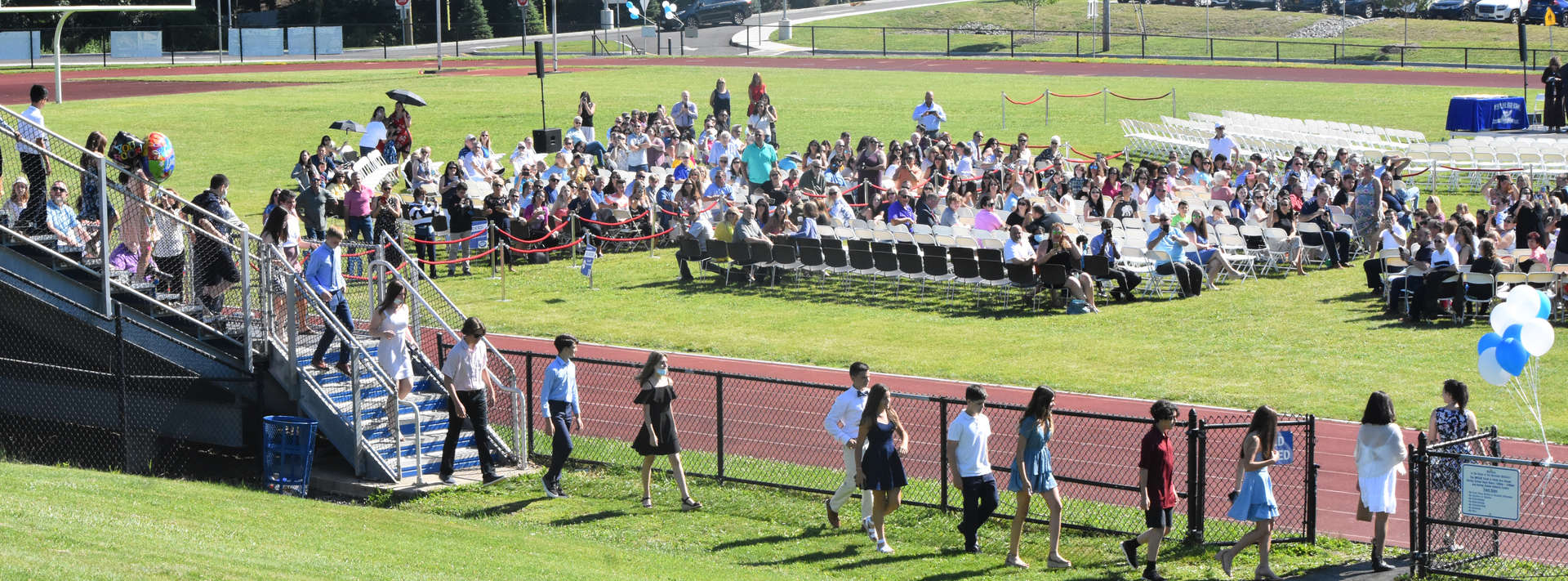 Students walk into stadium set up for graduation