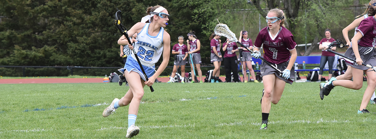 Girl lacrosse player running with ball.