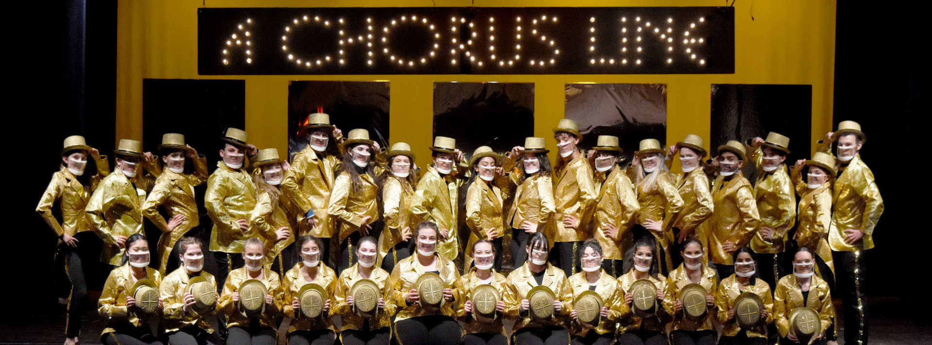 Student performers in gold jackets on stage in A Chorus Line
