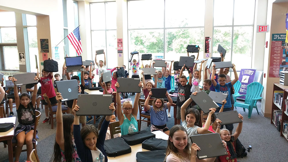 excited students holding laptops