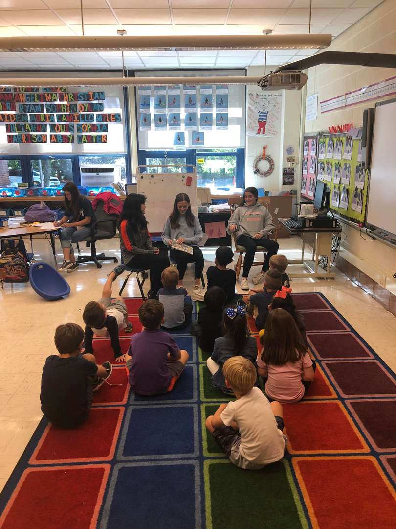 High school students reading to elementary school students
