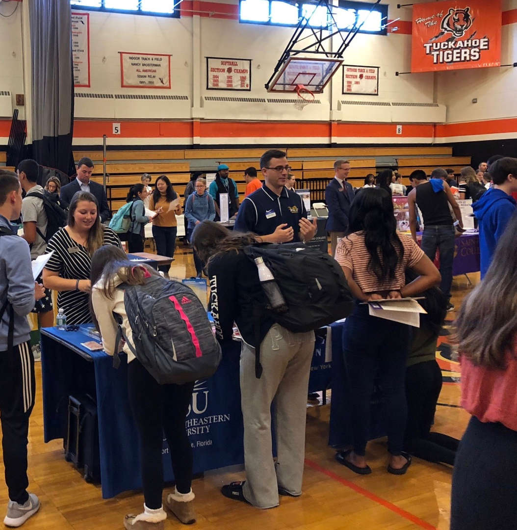 students talking to college representatives