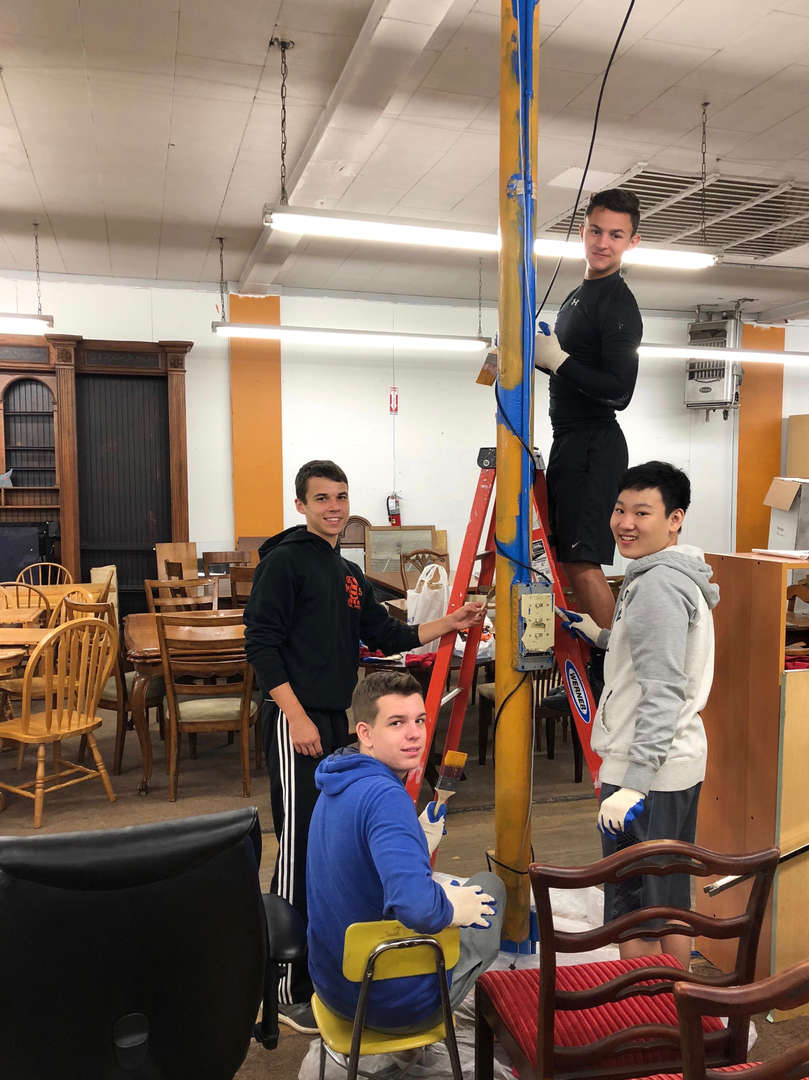 Students painting a pole