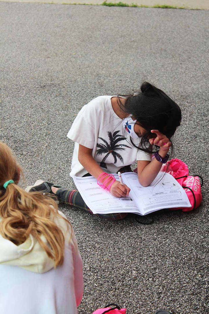 A female student completes a lesson in her workbook outside after running.