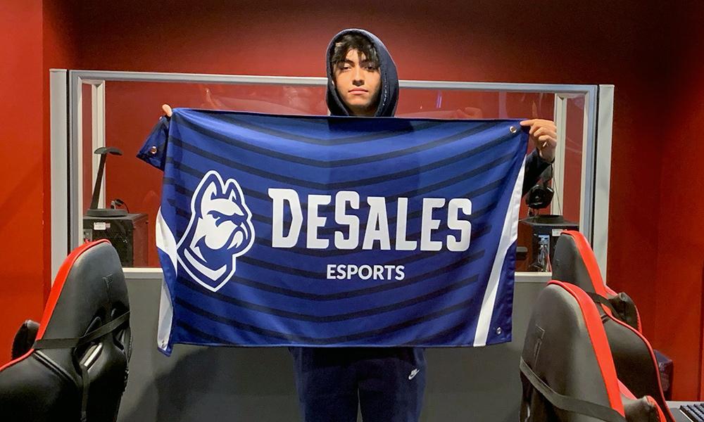 Morey holding a DeSales Esports flag