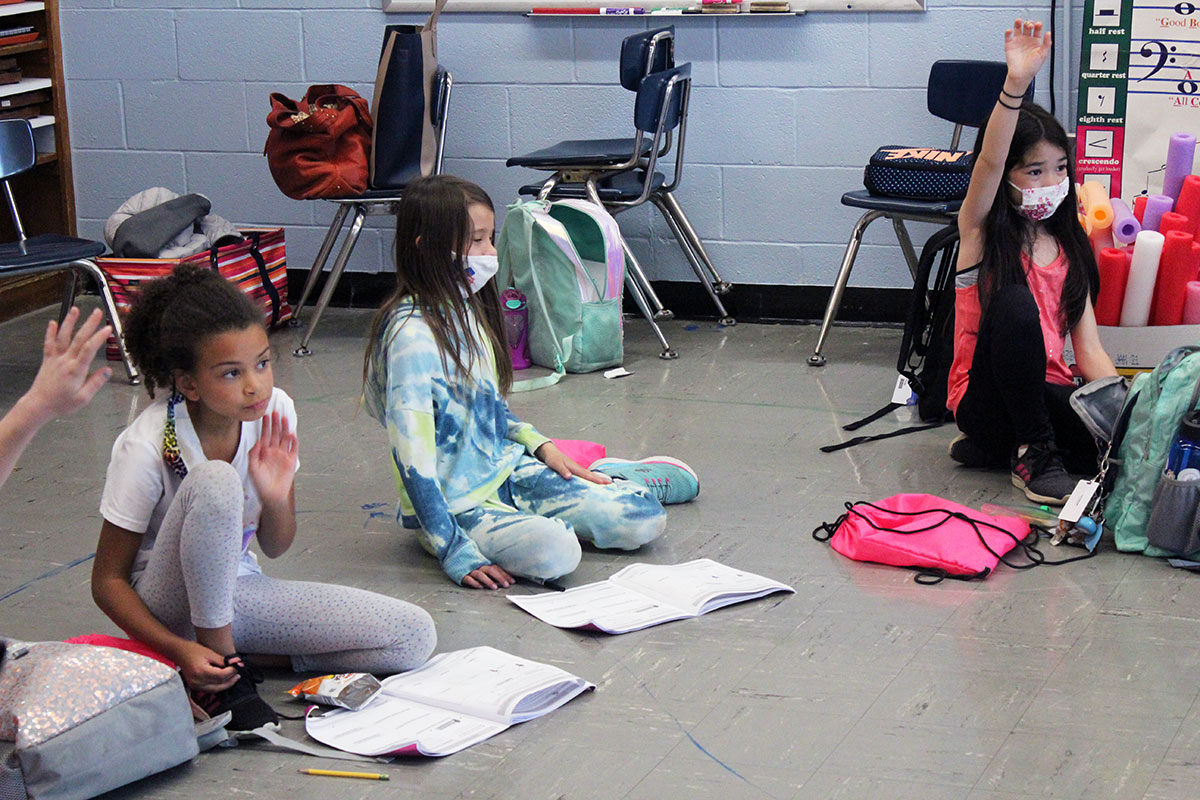 Students listen to a lesson while sitting on the floor.