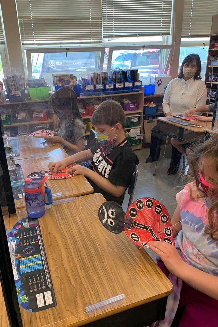 Students work with their ladybug clocks at their desks.