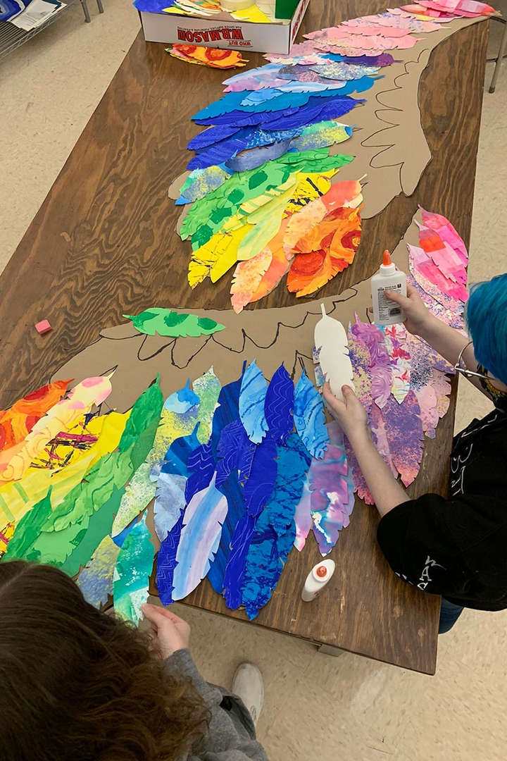 Students glue feathers together in the shape of wings.