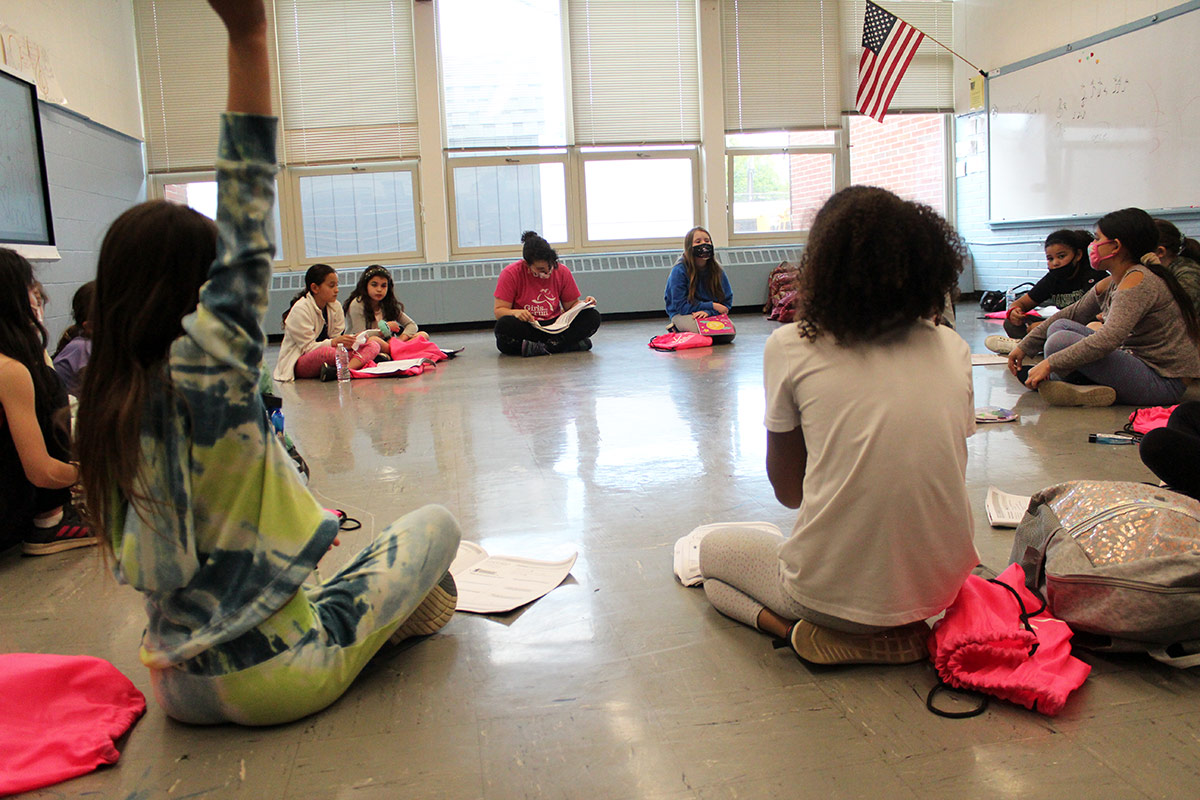 Girls sit in a circle on the floor listening to a lesson.