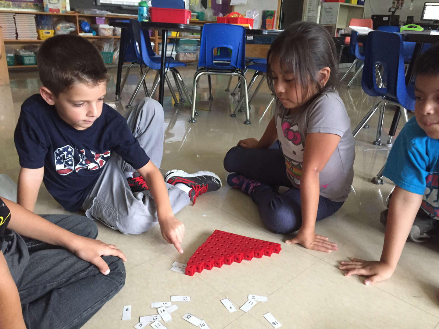 students building a triangle with math cubes