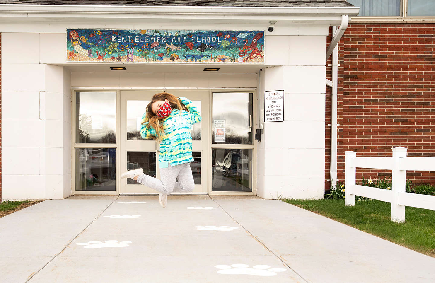 Student jumping in front of school entrance