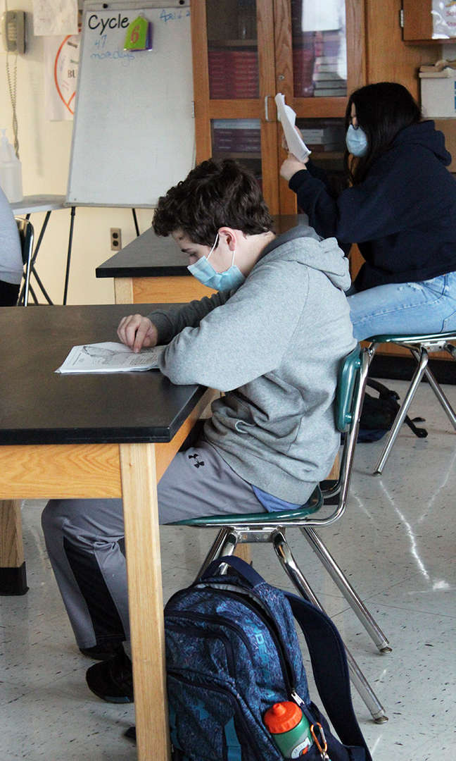 A male student studies a reference chart at his desk