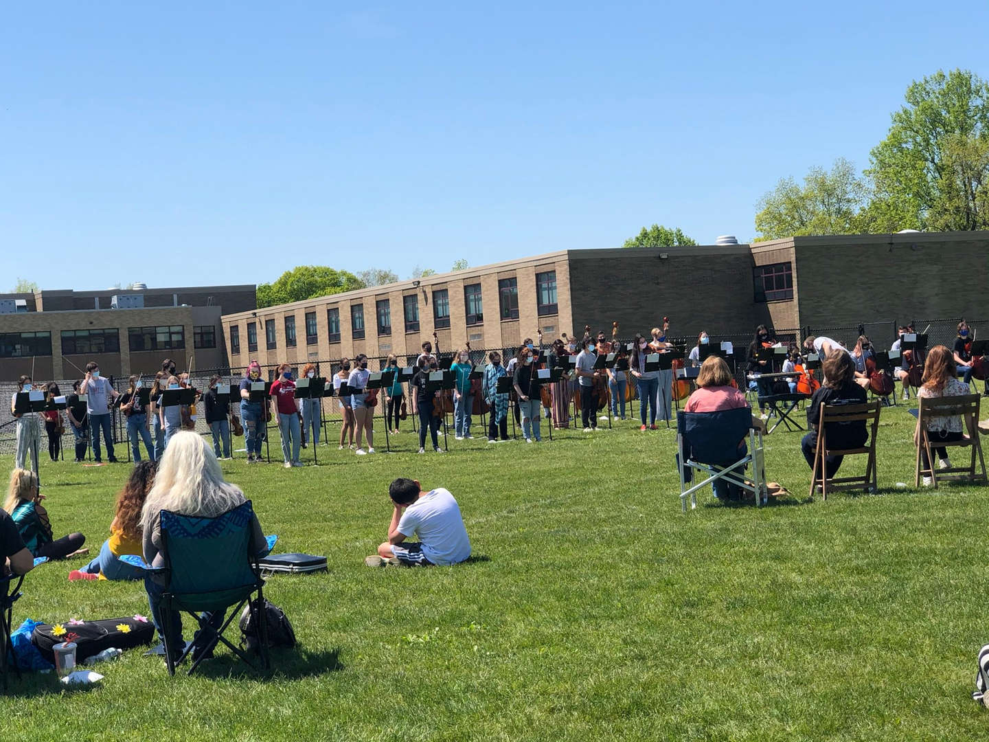 Student-musicians practice during open rehearsal on the field outside.