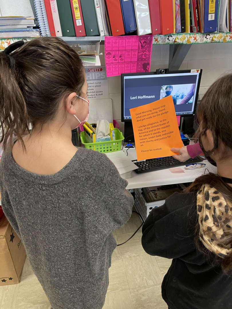 Two students stand in front of a computer screen reading the pledge