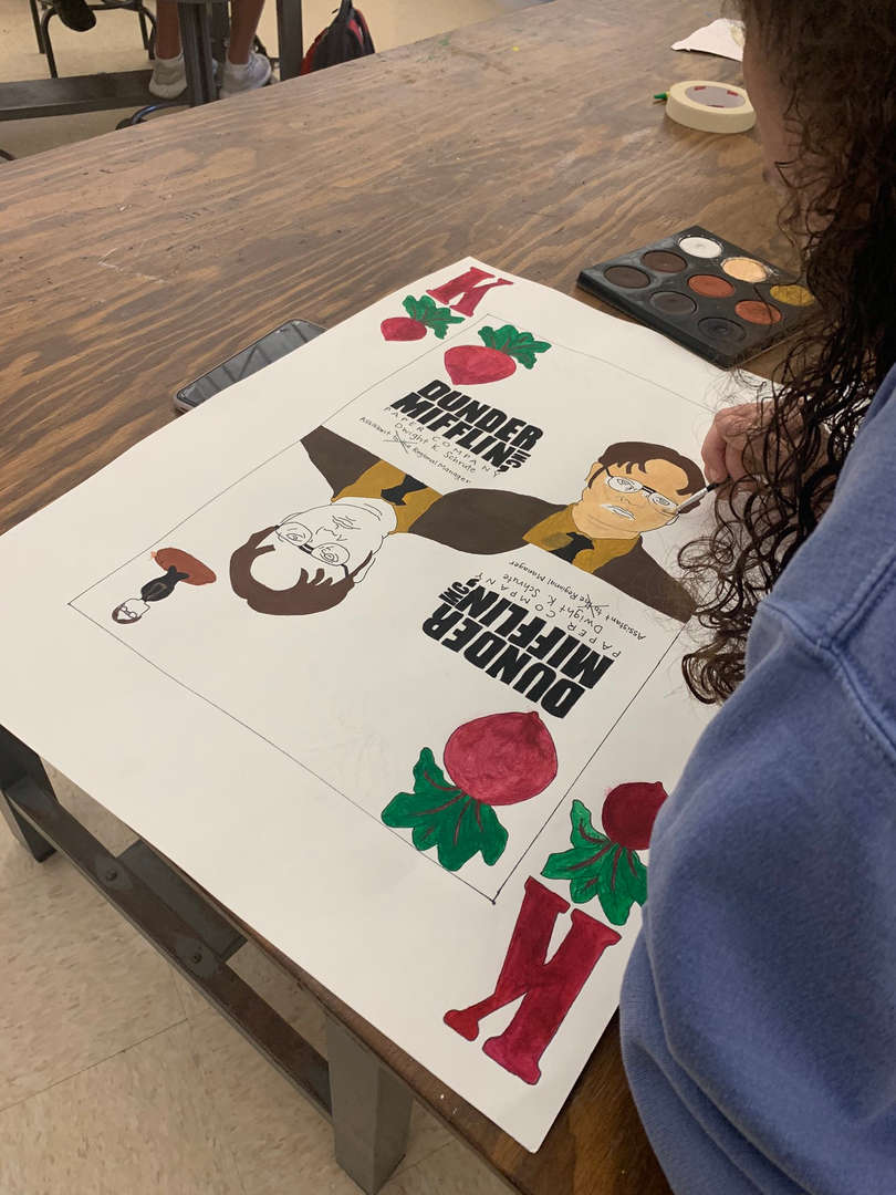 Student draws a character from the TV show The Office on a playing card