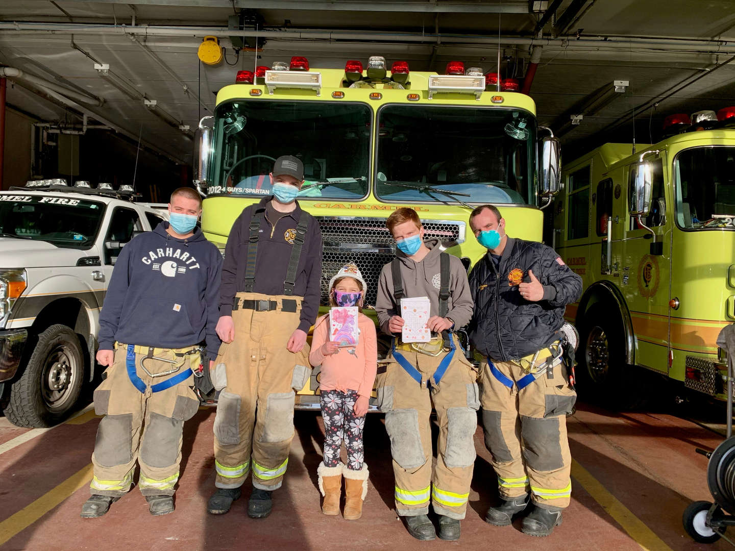 Students stand with firefighters in front of a fire truck