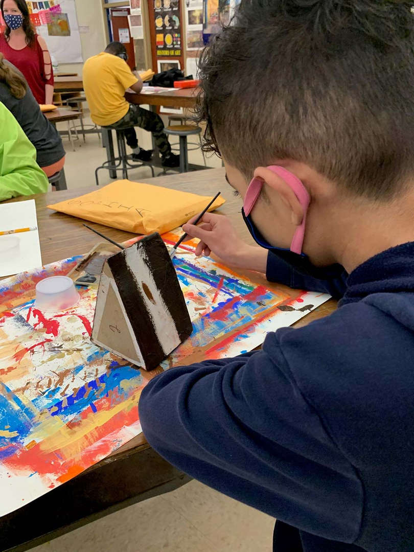 Student painting a slice of cake art piece