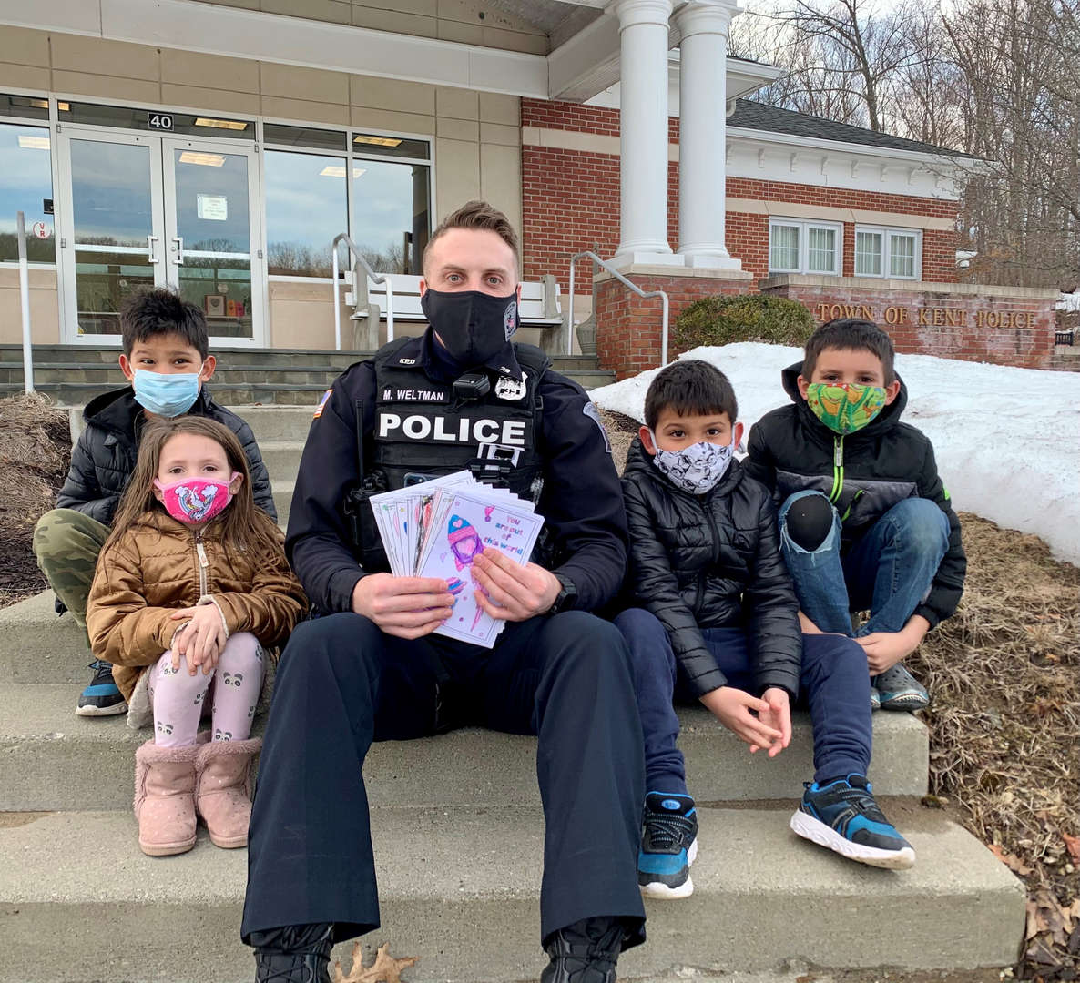 Students sit with a police officer who received a card