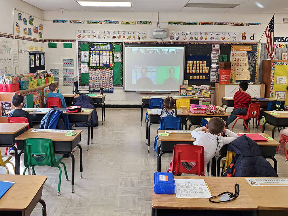 Students sit at desks watching a weather presentation on Zoom