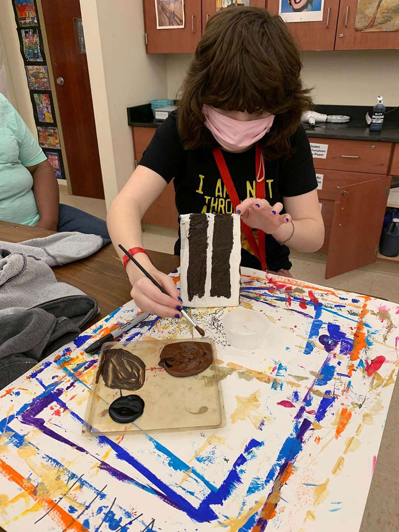 Student dips paint brush in brown paint on plate