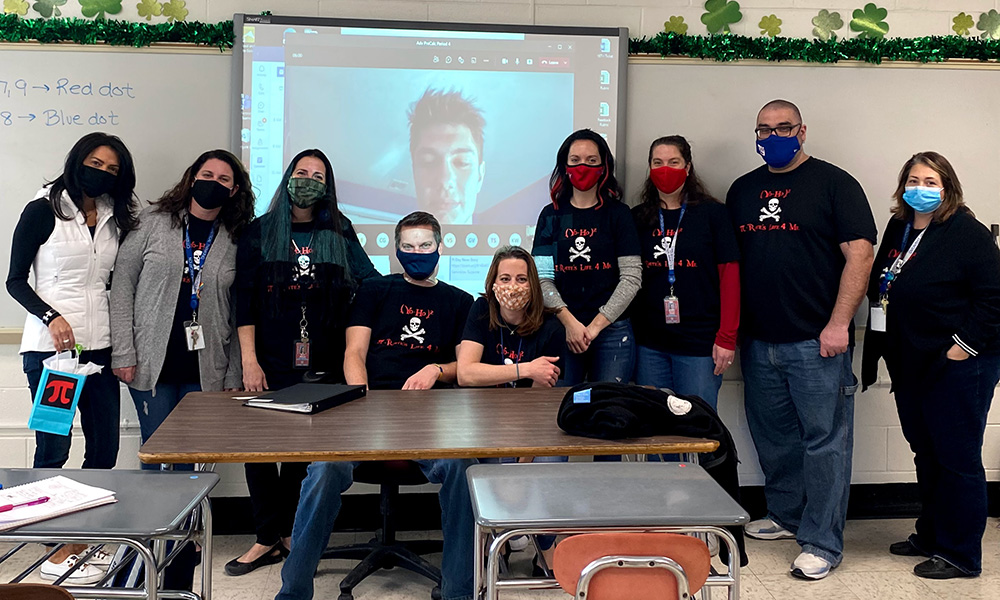 Nick DiLeo on screen surrounded by teachers