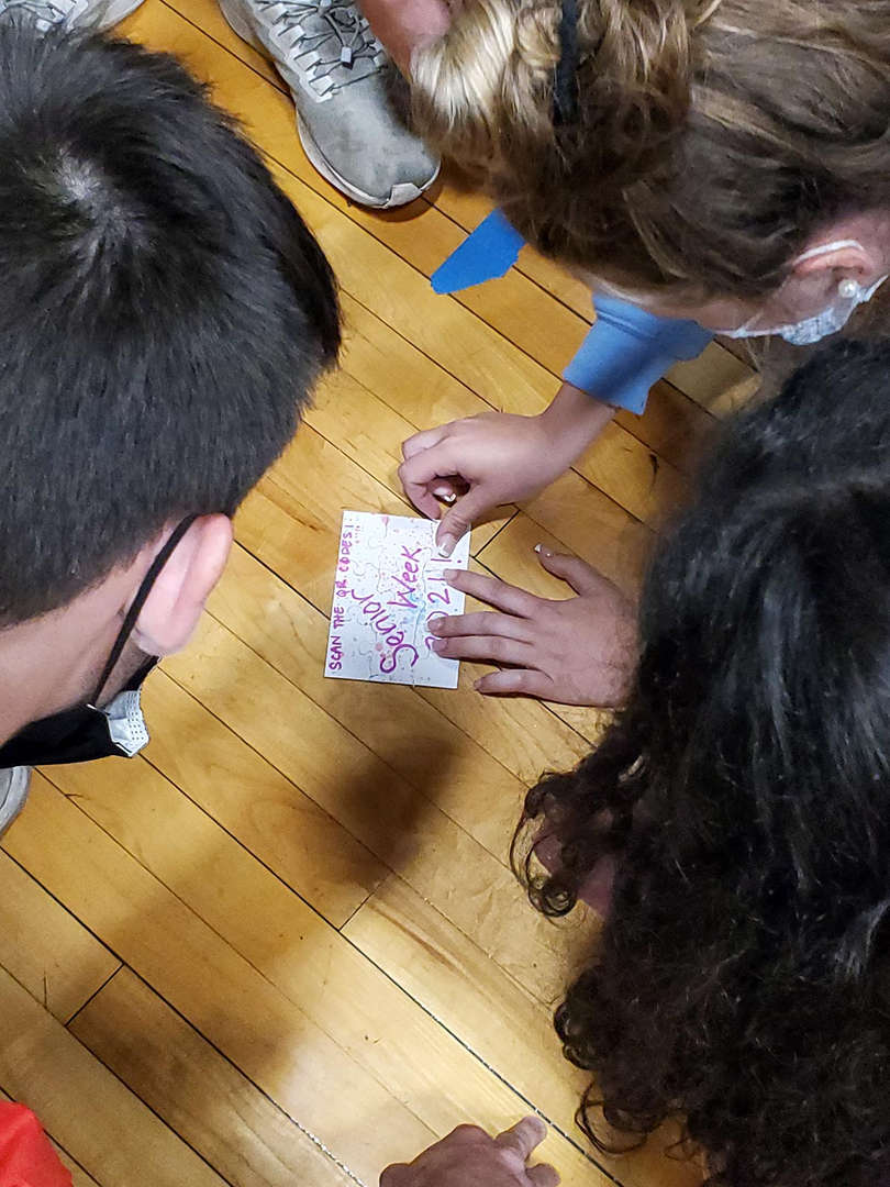 Students put together puzzle on the gym floor