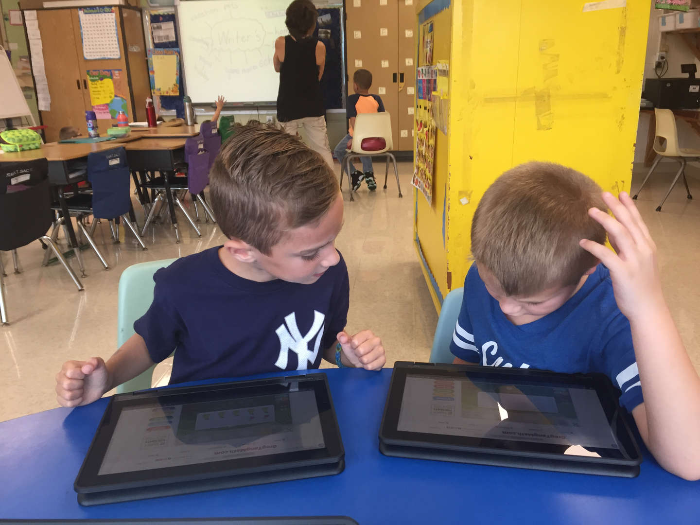 2 students working on math problems on iPads