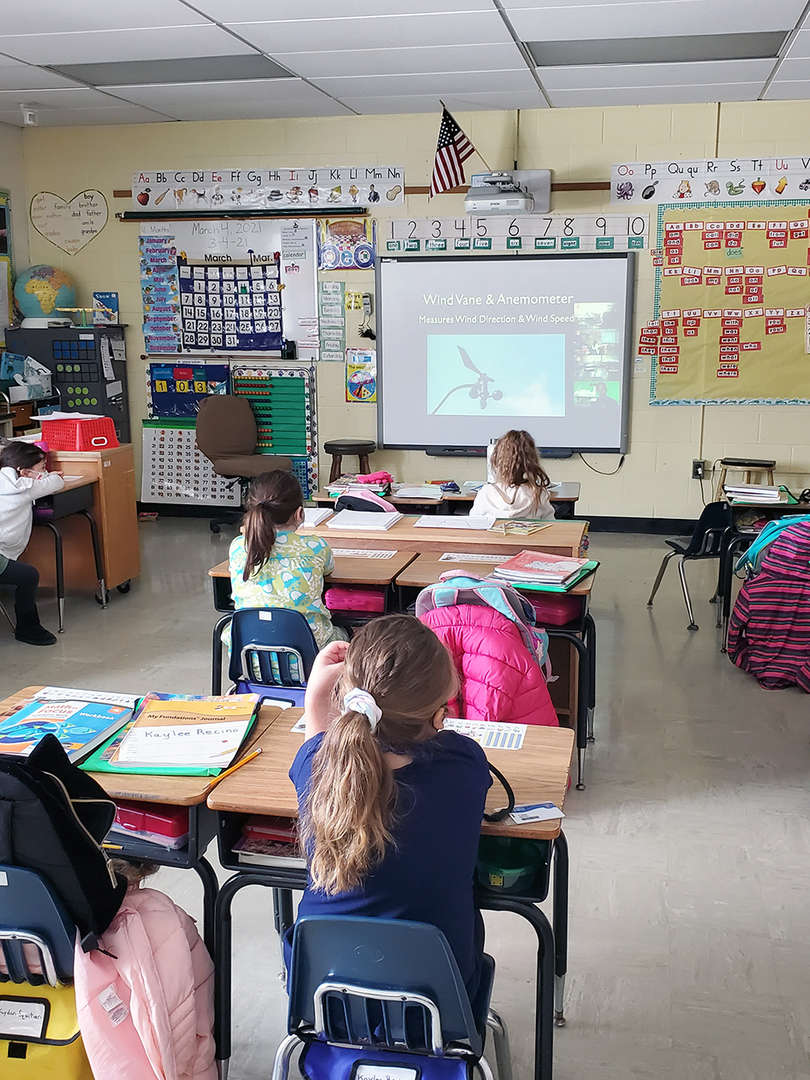 Students watch weather presentation on screen