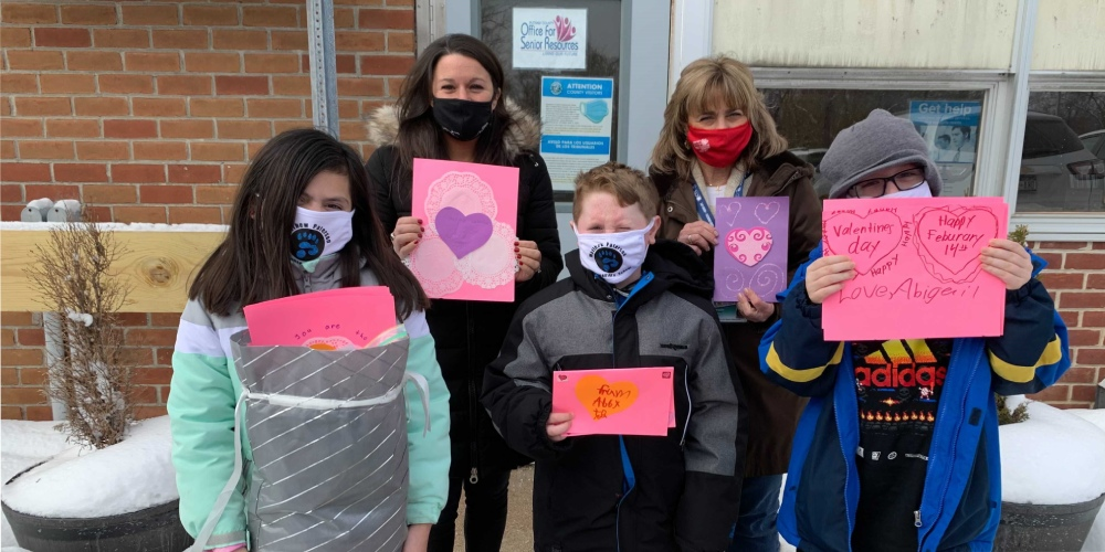 Students pose with Valentine's Day cards