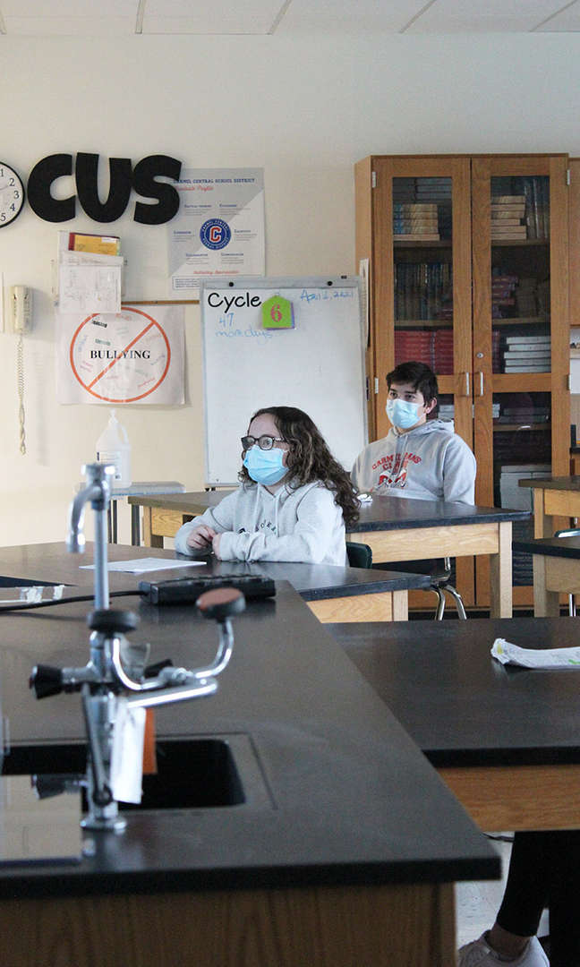 Female student wearing a mask sitting at a table with a male student wearing mask in background