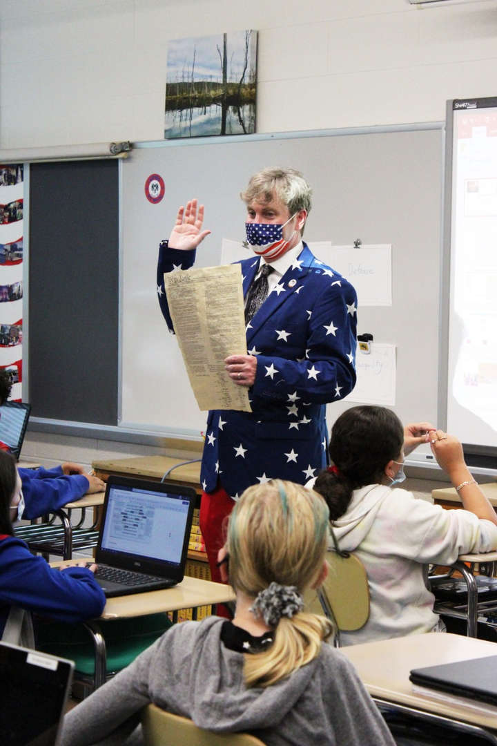 Teacher holds a copy of the Constitution