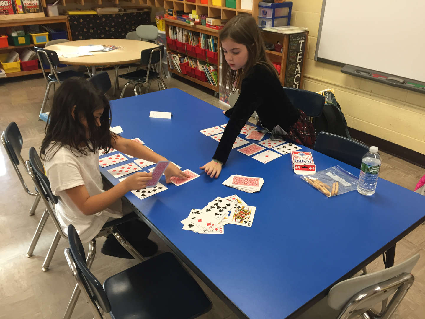 students learning math with playing cards