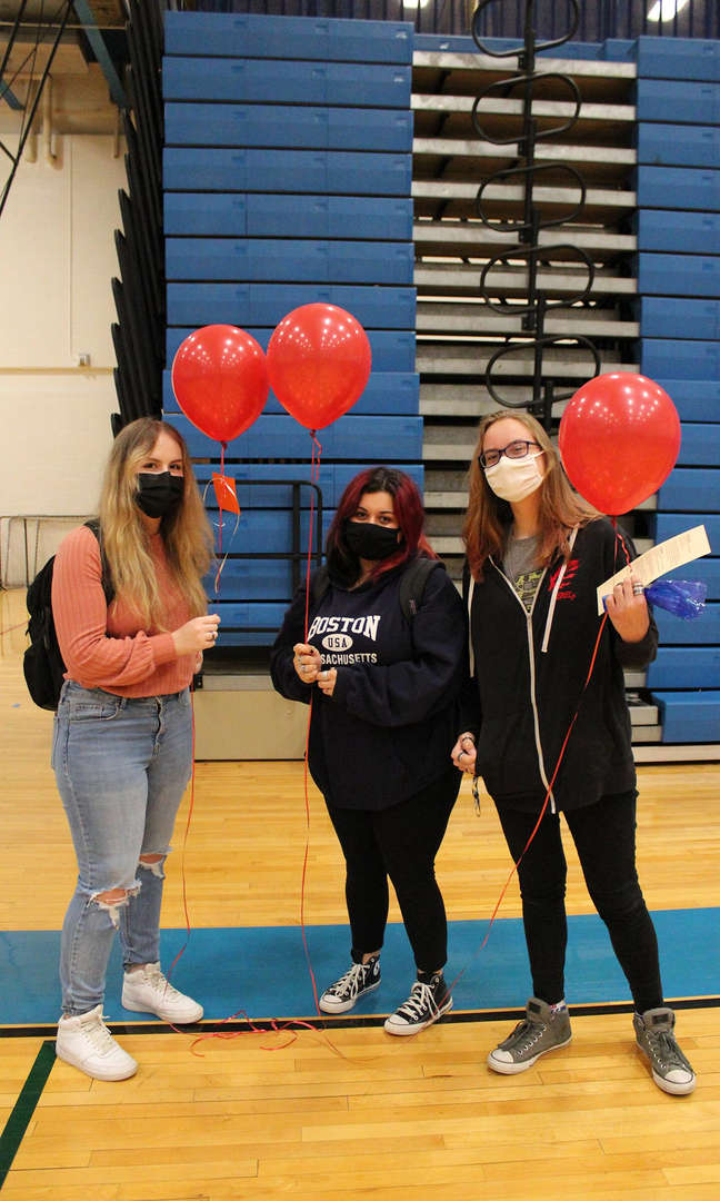 Three female students holding red balloons
