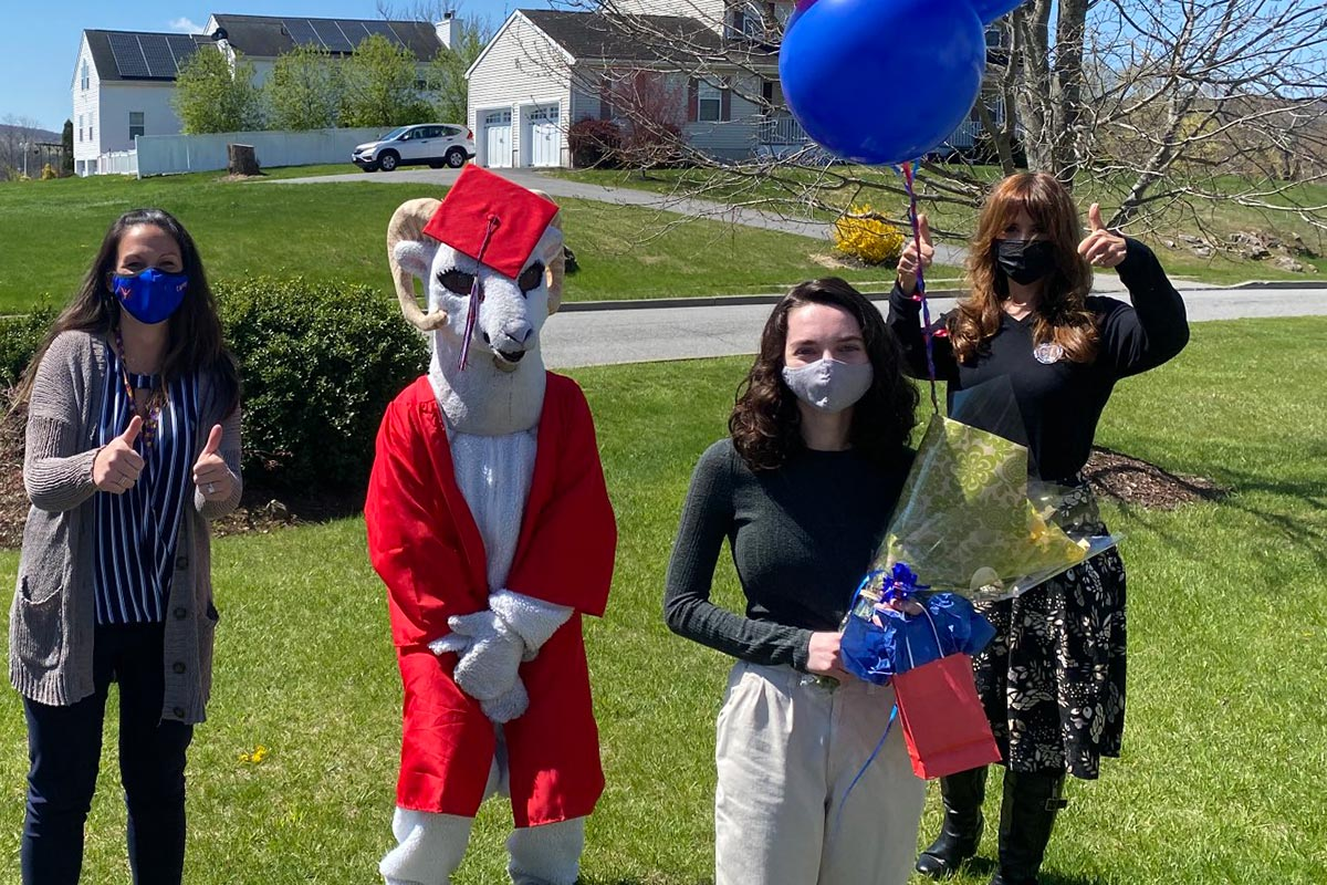Ariana Boswell surprised by school administrators and mascot at her home.