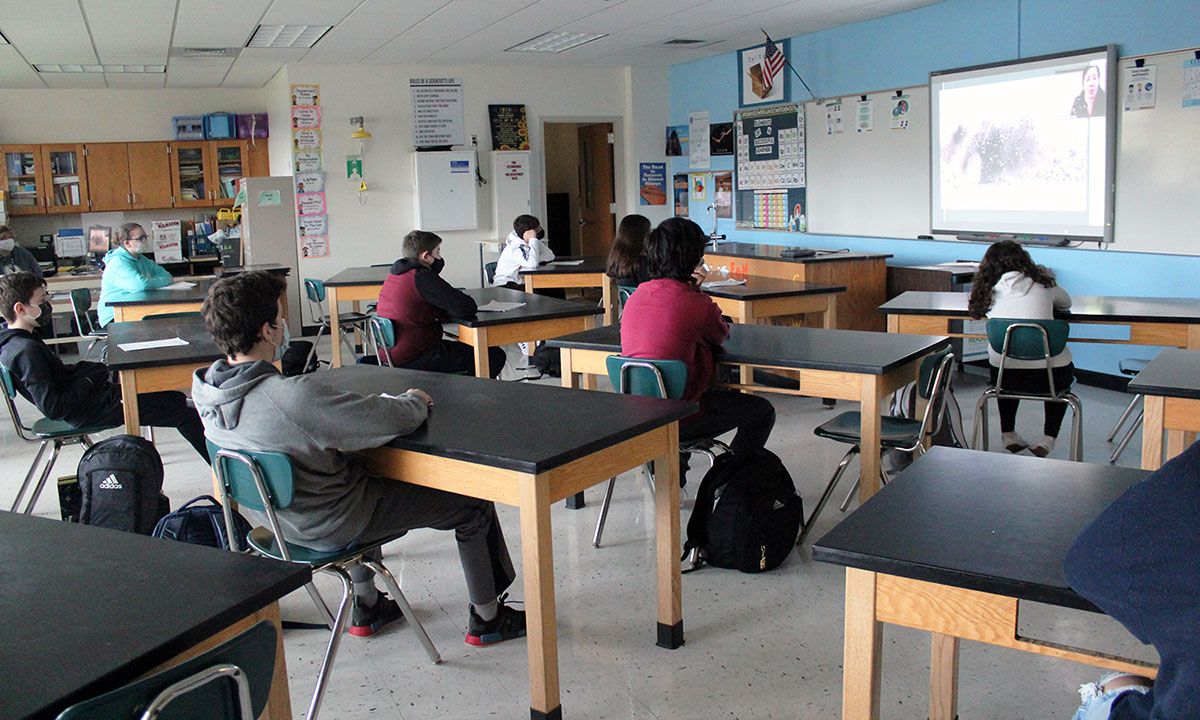 Students sit one per table in the classroom watching presentation
