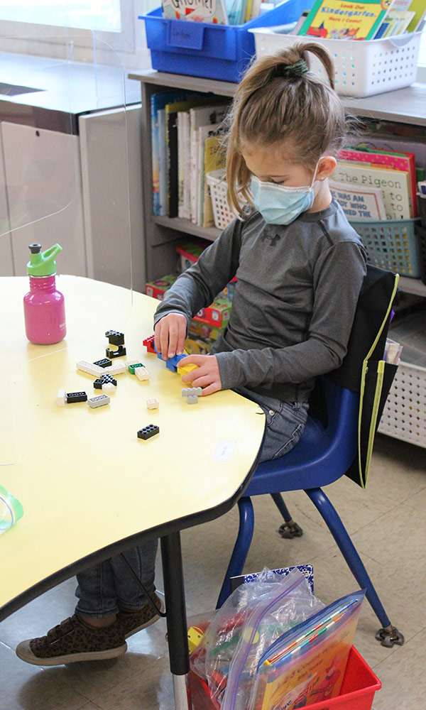 Kindergarten student works at a table with barriers around her.